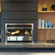 View of dark-toned indoor fireplace. - View of fireplace, hearth, black