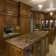 This is a master suite designed by Chuck cabinetry, ceiling, countertop, cuisine classique, estate, floor, flooring, hardwood, home, interior design, kitchen, room, under cabinet lighting, wood flooring, wood stain, brown