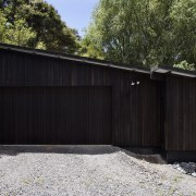 The timber for this house is treated with backyard, facade, fence, garage, garage door, house, outdoor structure, property, real estate, shed, siding, wood, yard, black