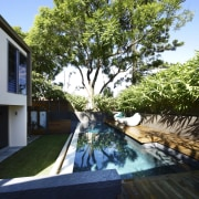 This house was designed by Kon Panagopoulos and backyard, home, house, outdoor structure, plant, property, real estate, resort, swimming pool, tree, water, yard, black