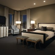 This master suite was designed by the Gary bed frame, bedroom, ceiling, floor, furniture, interior design, lighting, room, suite, wall, window, black