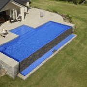 This is a view of the pool designed backyard, grass, house, lawn, leisure, outdoor furniture, property, real estate, roof, sunlounger, swimming pool, yard, brown