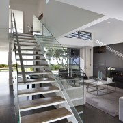 This house was designed by Hamish Cameron NZIA architecture, condominium, handrail, house, interior design, living room, real estate, stairs, gray