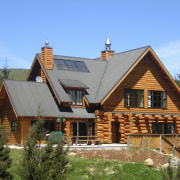 This large home efficiently uses solar energy thanks cottage, elevation, estate, facade, farmhouse, home, house, hut, log cabin, property, real estate, roof, siding, window, wood, teal, brown