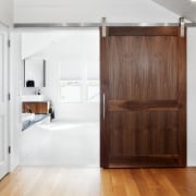View of entrance to bathroom with wooden sliding cabinetry, door, floor, hardwood, interior design, room, wood, white