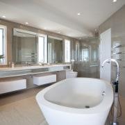 Bathroom with large white tub and beige walls. architecture, bathroom, bathtub, floor, interior design, plumbing fixture, real estate, room, gray