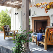View of patio with wooden seats and fireplace. backyard, cottage, courtyard, home, house, interior design, living room, outdoor structure, patio, porch, property, real estate, yard, gray