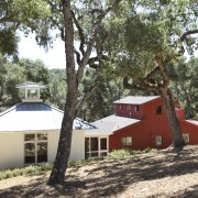 View of red and white buildings with trees. cottage, home, house, hut, plant, property, real estate, tree