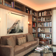 Lounge area with brown sofa and glass table, bookcase, furniture, home, interior design, library, living room, real estate, room, shelf, shelving, orange, brown