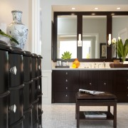 View of brown cabinetry with 3 rectangular mirrors. cabinetry, chest of drawers, coffee table, drawer, floor, flooring, furniture, hardwood, home, interior design, living room, room, shelf, shelving, table, gray, black