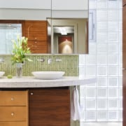 Walnut cabinetry lines the entry to this glass bathroom, bathroom accessory, bathroom cabinet, cabinetry, countertop, floor, home, interior design, kitchen, product, room, sink, tile, white