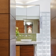 Walnut cabinetry lines the entry to this glass cabinetry, countertop, floor, interior design, kitchen, room, white, brown
