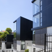 View of exterior with black and white walls. architecture, building, condominium, corporate headquarters, elevation, facade, home, house, residential area, teal