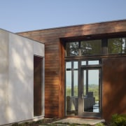 Exterior of house with rusted corten steel. Sustainable architecture, facade, home, house, real estate, siding, sky, window, teal
