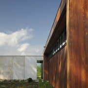 Exterior of house with rusted corten steel. Sustainable architecture, cloud, facade, grass, home, house, real estate, sky, sunlight, wood