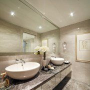 The mirror-fronted vanity in this glamorous suite continues bathroom, ceiling, estate, floor, home, interior design, real estate, room, sink, orange, brown