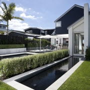 Here is a home designed by Belinda George architecture, condominium, corporate headquarters, estate, grass, home, house, property, real estate, reflecting pool, reflection, residential area, sky, swimming pool, villa, water