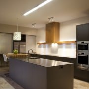 In this new kitchen, a breakfast bar in cabinetry, ceiling, countertop, cuisine classique, interior design, kitchen, room, under cabinet lighting, brown