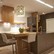 The David Trubridge lamp above this breakfast bar cabinetry, ceiling, countertop, cuisine classique, furniture, interior design, kitchen, light fixture, lighting, table, brown, orange