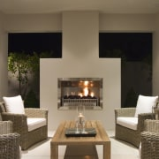 View of patio area at night with contemporary fireplace, hearth, home, interior design, living room, brown