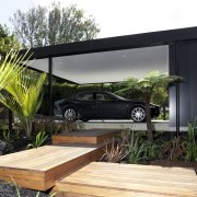 Exterior, garage, timber decking stairs, plants surround house. backyard, house, outdoor structure, real estate, roof, black