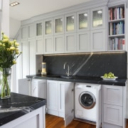 cabinet doors hide washing machine, dark splashback above cabinetry, countertop, cuisine classique, home, home appliance, interior design, kitchen, major appliance, room, gray
