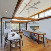 A long wooden kitchen island with seating at architecture, ceiling, daylighting, dining room, floor, flooring, hardwood, house, interior design, real estate, table, wood, wood flooring, gray