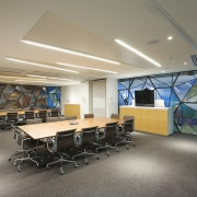 Boardroom with wooden tables and black seats. - architecture, ceiling, conference hall, institution, interior design, office, gray