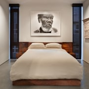 White bed with art on walls and portrait bed, bed frame, bedroom, exhibition, furniture, home, interior design, modern art, room, suite, wall, gray