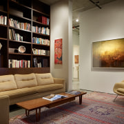 Lounge with floor rug, books on shelves and couch, floor, flooring, furniture, interior design, living room, room, shelving, table, wall, brown, black, gray