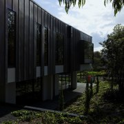 Exterior of house and garden. - Exterior of architecture, building, facade, grass, home, house, real estate, reflection, sky, sunlight, tree, black