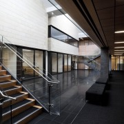 Stairs down to hallway with black seat. - architecture, building, daylighting, structure, black