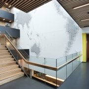 Stairs and landing with world design on wall. architecture, ceiling, daylighting, handrail, interior design, leisure centre, lobby, stairs, white