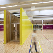 Indoor basketball court with lime and purple walls. architecture, floor, flooring, leisure centre, sport venue, sports, structure, wood, yellow, gray