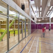 Indoor basketball court with lime and purple walls. architecture, daylighting, leisure centre, sport venue, structure, gray