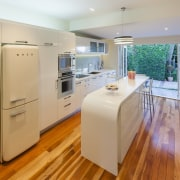 Contemporary kitchen with curved white island and wooden cabinetry, countertop, floor, flooring, hardwood, interior design, kitchen, laminate flooring, real estate, room, wood flooring, gray, orange