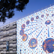 Art on parking building wall. - Art on architecture, blue, daytime, facade, landmark, mural, sky, structure, tree, wall, white, blue