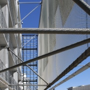 Close up of structure of parking building. - architecture, building, corporate headquarters, daylighting, daytime, facade, fixed link, line, metropolis, metropolitan area, sky, skyway, structure, urban area, gray