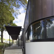 Exterior with curved windows. - Exterior with curved architecture, building, facade, house, reflection, tree, black, gray