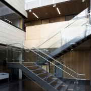Interior with stairs leading to grey tiled floor. architecture, building, condominium, daylighting, glass, handrail, interior design, lobby, stairs, structure, white, black