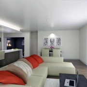 Lounge with cream couches and orange cushions. - architecture, ceiling, estate, home, interior design, living room, property, real estate, room, wall, gray