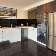 Kitchen with brown tiled flooring, stainless frige and cabinetry, countertop, cuisine classique, floor, flooring, home appliance, interior design, kitchen, property, real estate, room, white, black