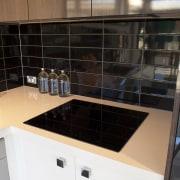 Black cooktop on white bench. - Black cooktop countertop, kitchen, room, sink, tile, black