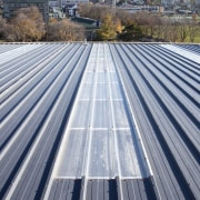 View of grey roof. - View of grey architecture, asphalt, daylighting, daytime, line, outdoor structure, roof, sky, solar panel, solar power, gray