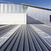 View of grey roof and grey building. - architecture, building, daylighting, energy, facade, fixed link, infrastructure, line, roof, sky, sport venue, structure, gray