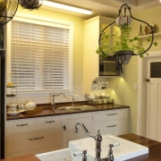 white sink integrated into island, hanging pot plants ceiling, countertop, home, interior design, kitchen, lighting, room, under cabinet lighting, window, brown, orange