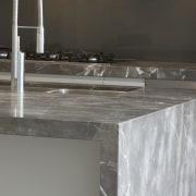 Grey and brown marble island benchtop, white walls, countertop, floor, plumbing fixture, sink, tap, gray, black