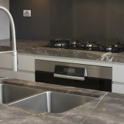 Grey and brown marble island benchtop, white walls, countertop, floor, flooring, kitchen, kitchen stove, sink, tap, tile, gray, black