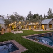 Rustic house modelled on French barn. Interiors feature backyard, cottage, estate, farmhouse, hacienda, home, house, landscape, landscaping, leisure, lighting, property, real estate, reflection, residential area, resort, swimming pool, villa, yard, white, brown