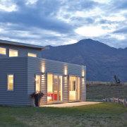rear of house lit at dusk - rear cottage, elevation, facade, farmhouse, home, house, landscape, log cabin, property, real estate, siding, sky, teal, blue